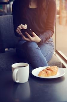 Femmina asiatica digitando un messaggio di testo con caffè e croissant
