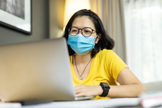 Femmina asiatica che per mezzo del computer portatile durante la quarantena alla casa.