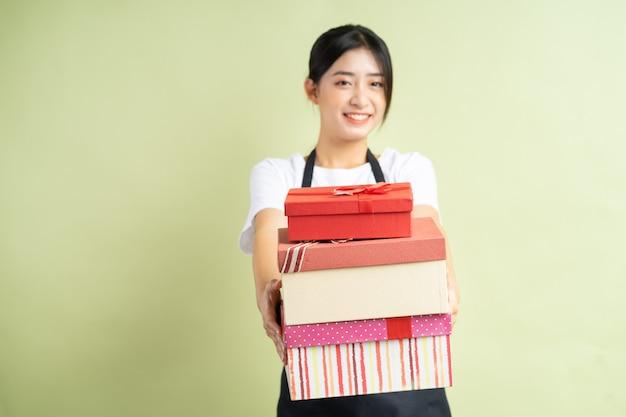 Cameriera asiatica che tiene in mano una confezione regalo