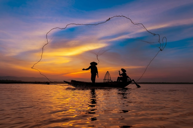 Pescatore asiatico con la sua barca di legno nel fiume della natura al mattino presto prima dell'alba