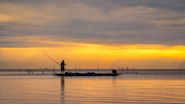 Pescatore asiatico sulla barca di legno per la cattura del pesce nel lago al mattino