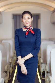 Assistente di volo asiatico che posa con il sorriso al centro del corridoio all'interno del sedile del passeggero dell'aereo sullo sfondo