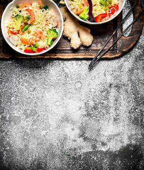 Cibo asiatico. tagliatelle cinesi con verdure. su fondo rustico.