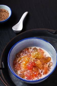 Concetto di cibo asiatico krong krang dessert dolci gnocchi d'attualità nel latte di cocco in tazza di ceramica