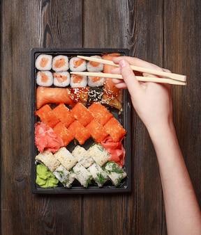 Sushi di prelibatezza di cibo asiatico e bacchette di legno rotoli sul tavolo