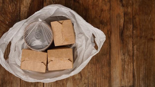 Consegna di cibo asiatico. cibo in contenitori e in un pacchetto su uno sfondo di legno. imballaggio di cibo e sushi giapponese.