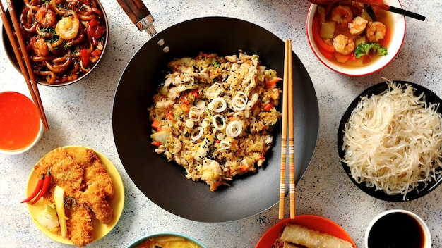 Cibo asiatico servito. piatti, padelle e ciotole piene di gustosi piatti orientali, riso fritto con spezie