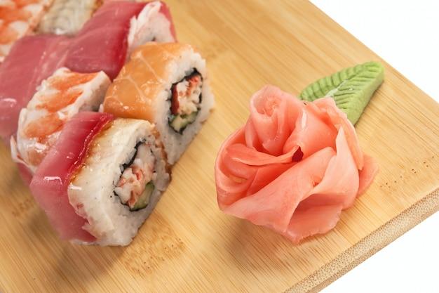 Sushi asiatici dell'alimento sul piatto di legno isolato su fondo bianco