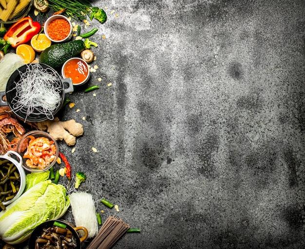 Cibo asiatico. una varietà di ingredienti per cucinare cibo cinese o tailandese su uno sfondo rustico.