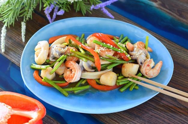 Cibo asiatico con frutti di mare, verdure in salsa di soia su un piatto