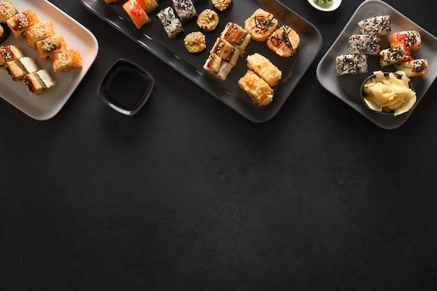 Cibo asiatico con sushi impostato su sfondo nero. vista dall'alto. lay piatto. consegna del cibo.
