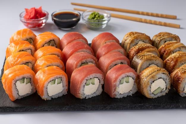 Cibo asiatico con sushi set di salmone, tonno e anguilla con formaggio philadelphia su una tavola di ardesia su sfondo bianco. servito con salsa di soia, wasabi e zenzero sottaceto. avvicinamento.
