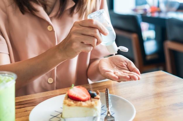 Ragazza asiatica che applica gel igienizzante sulla sua mano prima di mangiare