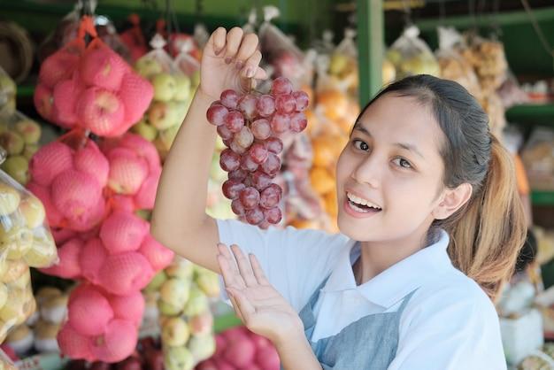 Ragazza asiatica in un grembiule che tiene l'uva in bancarelle di frutta, concetto di frutta fresca