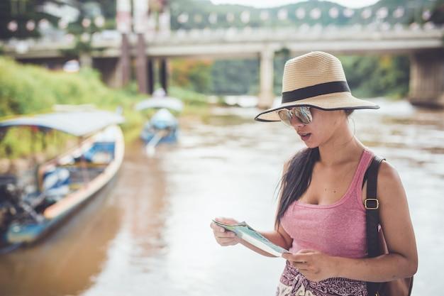 La ragazza asiatica compra una pipa per il viaggio per andare in crociera