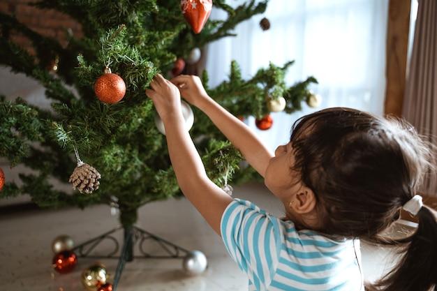 Ragazza asiatica che decora l'albero di natale a casa