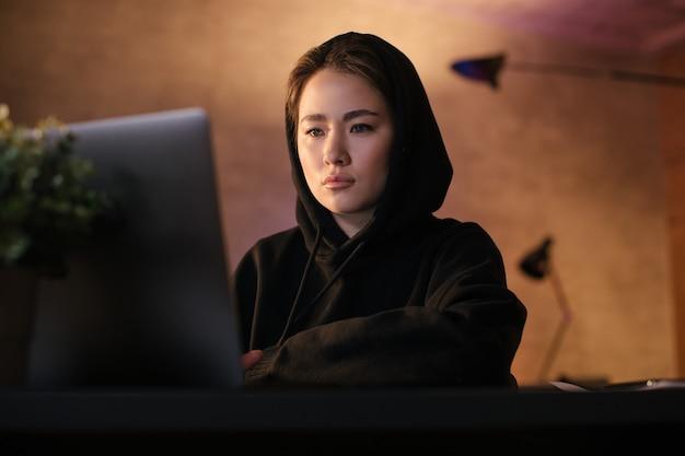 Libero professionista asiatico della ragazza che lavora ad un computer portatile