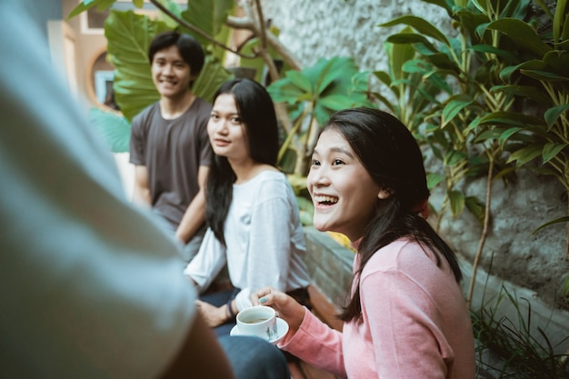 Ragazza asiatica e amici sorridenti e seduti a bere caffè e godersi insieme al caffè