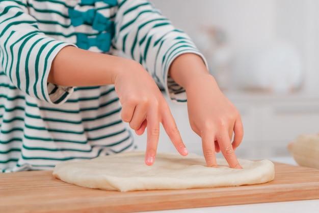 Ragazza asiatica che si diverte usando il dito per impastare la pasta e preparare la panetteria in cucina.