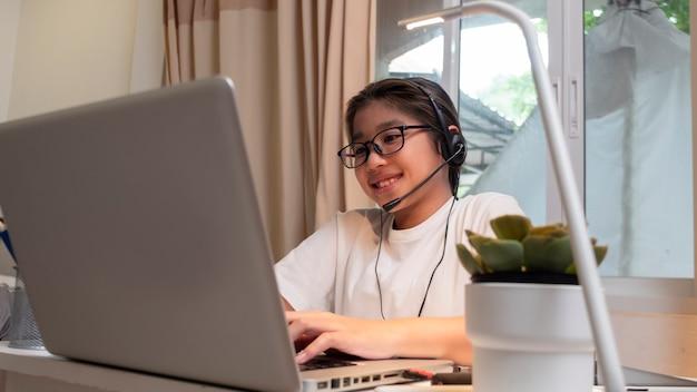 La ragazza asiatica in cuffia si siede alla scrivania studia online sul laptop i bambini indossano le cuffie che imparano usando le lezioni di internet in quarantena studenti che imparano le lezioni online di internet virtuale dalla scuola a causa del covid19