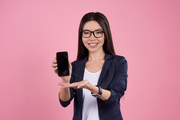 La ragazza asiatica sta proponendo con il telefono nero in vetri.