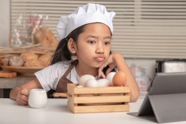 Una ragazza asiatica sta guardando come preparare un panificio da un computer portatile