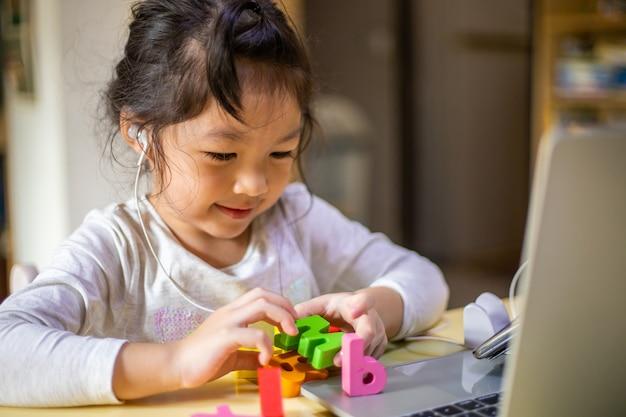Ragazza asiatica che impara alfabeti in linea, ragazza felice impara in linea con il computer portatile a casa.