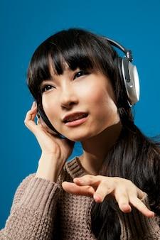 Ragazza asiatica ascolta musica su sfondo blu studio