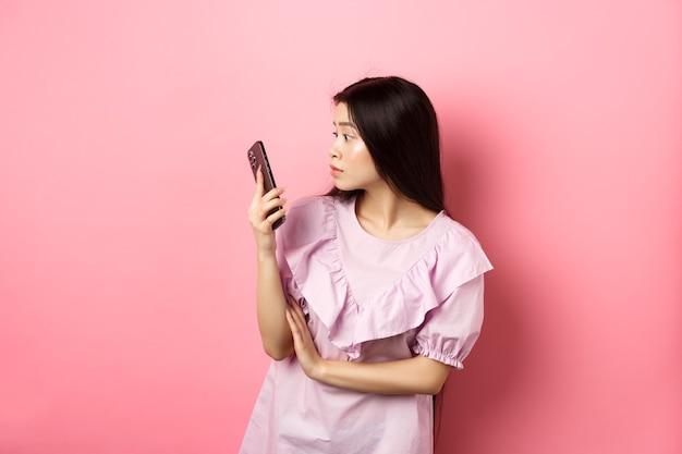 La ragazza asiatica guarda sorpreso dallo schermo dello smartphone, leggendo il messaggio, in piedi in abito su sfondo rosa.