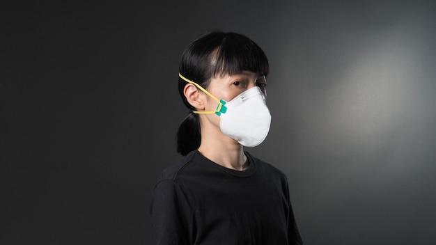 Ragazza asiatica in maschera su sfondo nero in situazione di quarantena di coronavirus titolo su