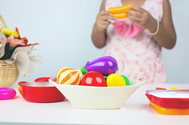 Ragazza asiatica che gioca cucina del giocattolo.