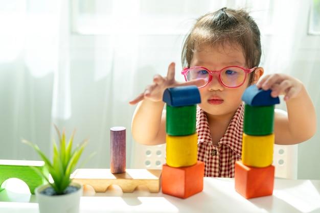Ragazza asiatica che gioca il blocco di legno nel soggiorno