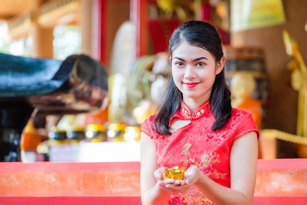 Ragazza asiatica in abito rosso, etnia cinese benedetta con l'oro in mano.