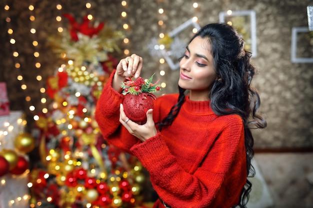 Ragazza asiatica in un maglione rosso che tiene un palloncino giocattolo di natale