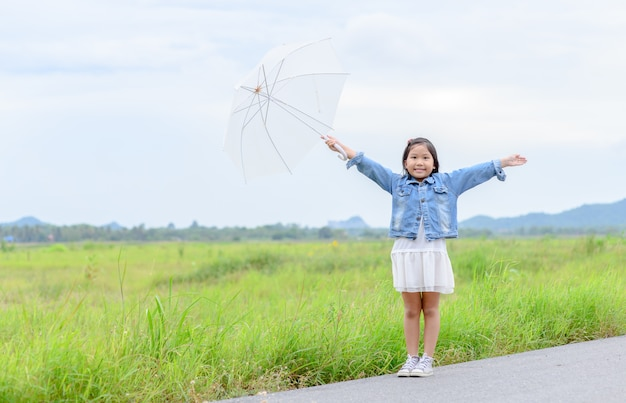 Sorriso di ragazza asiatica e tenendo l'ombrello bianco