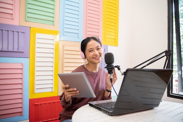 Una ragazza asiatica che parla in un microfono mentre registra un video blog utilizzando un pad e un computer portatile