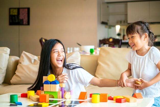 La ragazza asiatica trascorre del tempo insieme per giocare a blocchi di legno con sua sorella in salotto a casa.