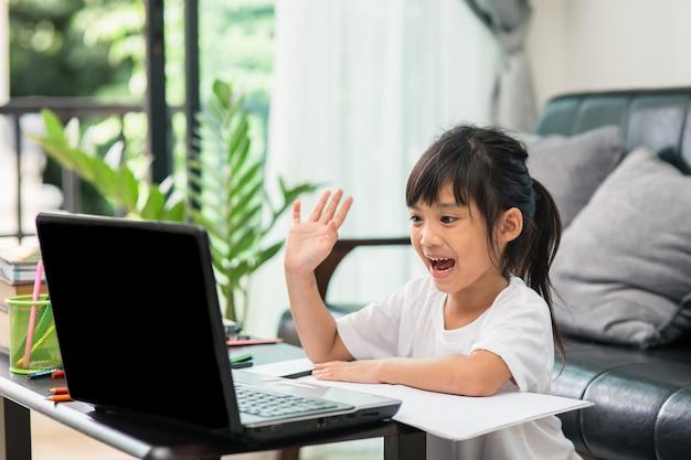 Studentessa asiatica studentessa online che studia lezione online videochiamata zoom insegnante, ragazza felice impara la lingua inglese online con il laptop a casa. nuovo normale. covid-19 coronavirus. distanza sociale. resta a casa