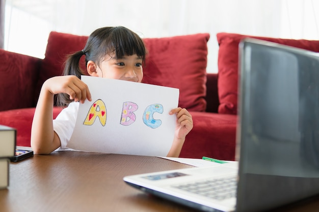 Studentessa asiatica in linea di apprendimento della classe studia online con il computer portatile a casa.