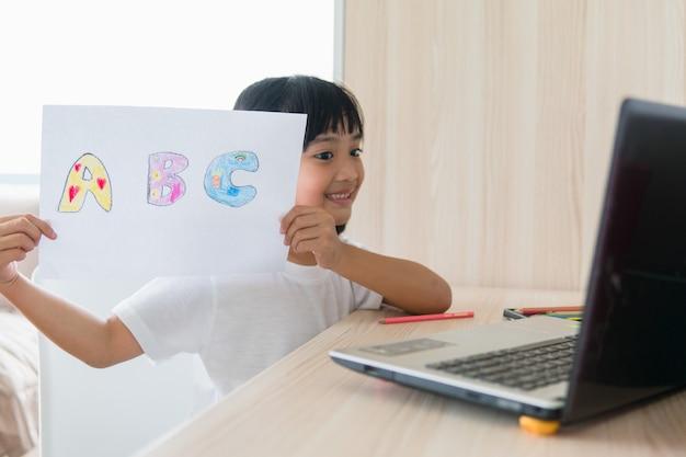 Lezioni di apprendimento online di una studentessa asiatica studiano online con il laptop a casa.