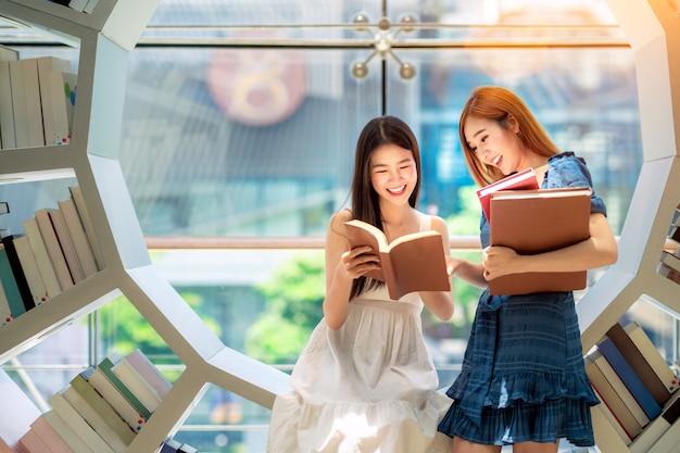 La studentessa asiatica ha letto un libro di testo in biblioteca nella sua università