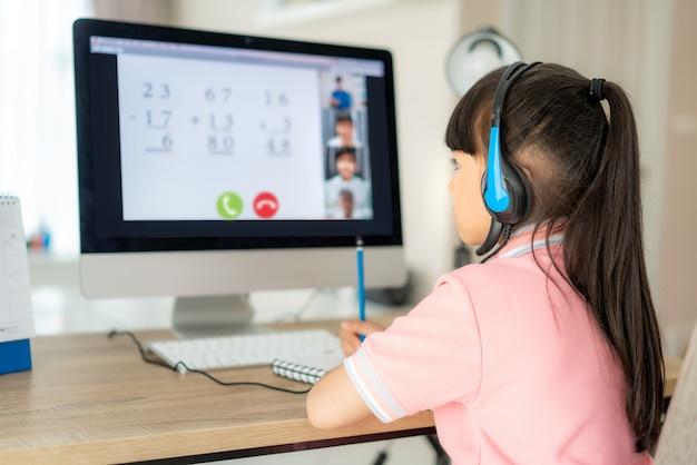 E-learning asiatico della videoconferenza della studentessa con l'insegnante e compagni di classe sul computer in salone a casa. homeschooling e apprendimento a distanza, online, istruzione e internet.