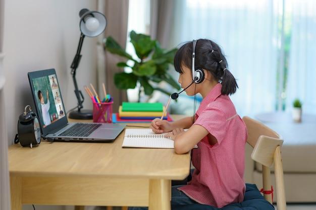 Videoconferenza studentessa asiatica e-learning con insegnante e compagni di classe sul computer in salotto a casa
