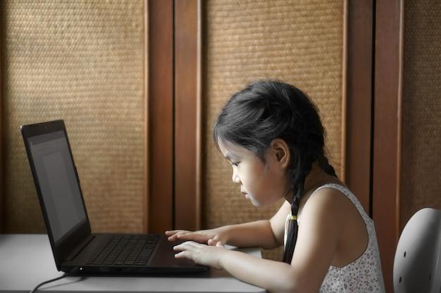 La ragazza asiatica studia online da casa sul taccuino del computer o gioca il computer portatile sullo scrittorio