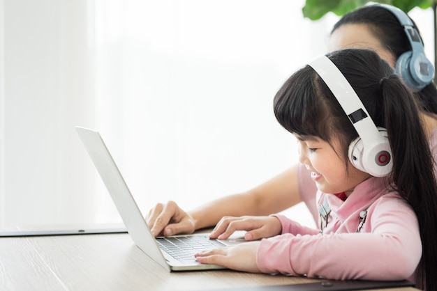 Ragazza asiatica che studia con laptop e auricolare, corso per corrispondenza con allontanamento sociale