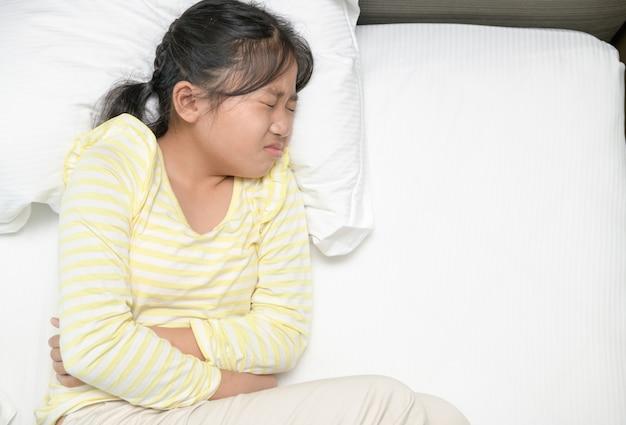 Ragazza asiatica che soffre di mal di stomaco e sdraiata sul letto. diarrea o concetto sano