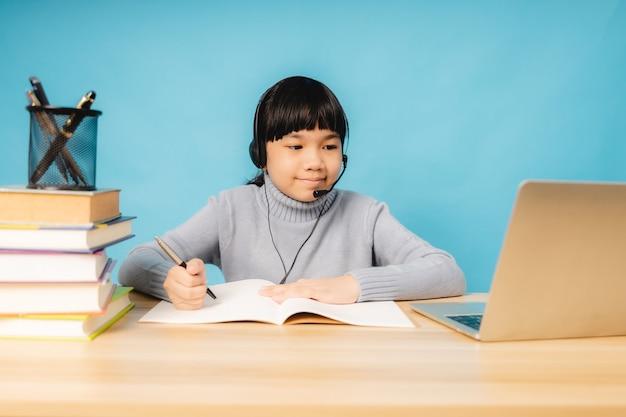Ragazza asiatica parla e impara online su laptop con sfondo blu