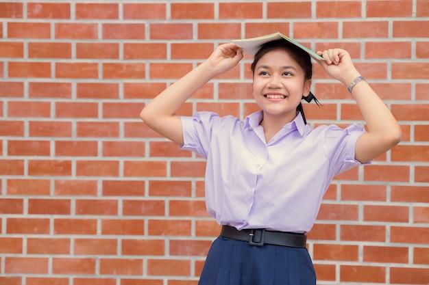 Sorriso felice dell'uniforme teenager dell'allievo della ragazza asiatica con il libro per l'istruzione di nuovo al concetto della scuola.