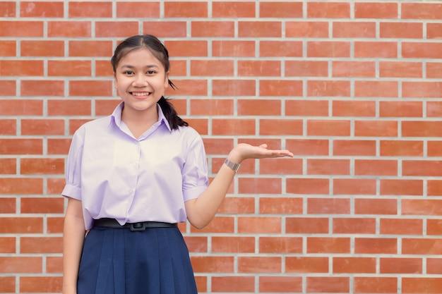 Sorriso felice dell'uniforme teenager dell'allievo della ragazza asiatica con il presentatore della mano che mostra lo spazio della copia della parete dell'esposizione.