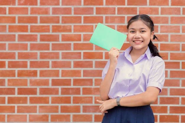 Ritratto sorridente felice dell'uniforme teenager dell'allievo della ragazza asiatica con il libro per l'istruzione di nuovo al concetto della scuola.